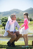 Daughter and father in fairy costume interacting with each other. At garden on a sunny day Royalty Free Stock Image