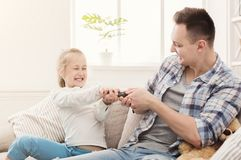 Daughter and father fighting for remote control stock image