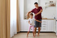 Daughter and father having fun and dancing in the kitchen, people wearing casual clothing, man raising small girl pigtails, happy