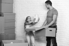 Daughter and father hold box, white teddy bear and unpack or pack. New home and family. Girl and man with happy faces. Daughter and father hold box, white teddy royalty free stock photos