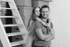 Daughter and father near ladder and pile of boxes. Girl and men with smiling faces on white brick wall background. Kid hugs her dad. New home, moving in and stock photo