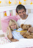 Daughter and father playing with a stethoscope Royalty Free Stock Photo