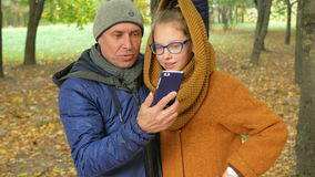 Daughter and father talking on the phone in the autumn park on the video. Dad smiles and laughs with her daughter a stock footage