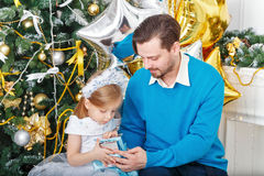 Daughter and father unpacked gifts at the Christmas tree. Royalty Free Stock Photos