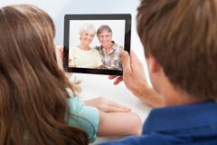 Daughter with father video chatting on digital tablet Royalty Free Stock Images