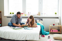Daughter and father writing composition together Royalty Free Stock Photo