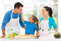 Daughter feeding father. Cute little daughter feeding father a piece of tomato in kitchen Stock Photos