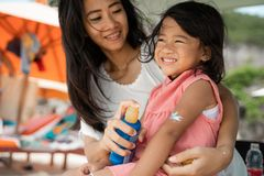 A daughter feels amused when mother give a sunblock to his arm. When holiday on the beach stock image