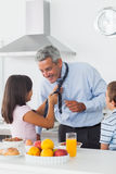 Daughter fixing her fathers tie with son in the kitchen. At home in the morning Stock Images
