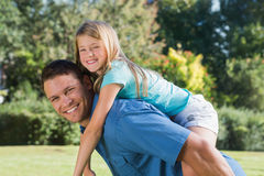 Daughter getting piggy back from dad Stock Photos