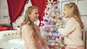 Daughter gives a gift to her mother for the new year Stock Photos