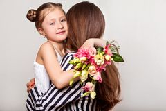 Daughter gives her mother flowers in the studio, happy mother`s. Day stock images