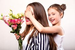 Daughter gives her mother flowers in the studio, happy mother`s. Day stock photo