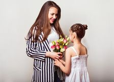 Daughter gives her mother flowers in the studio, happy mother`s. Day stock image