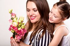 Daughter gives her mother flowers in the studio, happy mother`s. Day royalty free stock photography