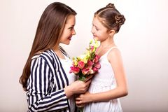 Daughter gives her mother flowers in the studio, happy mother`s. Day royalty free stock images