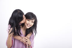 Daughter gives her mum a kiss. Mother and Daughter happy pose isolated on white Stock Photos