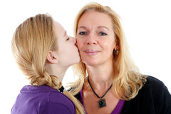 Daughter gives mother a kiss on the cheek Stock Images