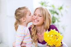 Daughter giving flowers and kiss to smiling happy mohter Royalty Free Stock Images