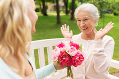 Daughter giving flowers to senior mother at park Stock Photography