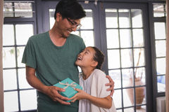 Daughter giving gift box to father in living room Stock Images