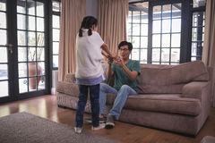 Daughter giving gift box to father in living room Royalty Free Stock Images