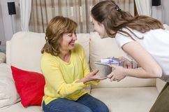 Daughter is giving a gift her mother in the Mother`s day. Stock Photo