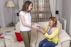 Daughter is giving a gift her mother in the Mother`s day. Royalty Free Stock Images