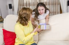 Daughter is giving a gift her mother in the Mother`s day. Stock Images