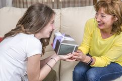 Daughter is giving a gift her mother in the Mother`s day. Royalty Free Stock Photography