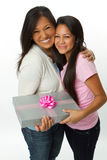 Daughter giving a gift to her mom. Stock Photos