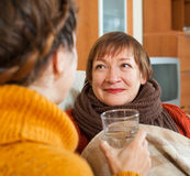 Daughter giving the glass of water to  mature mother Stock Photos