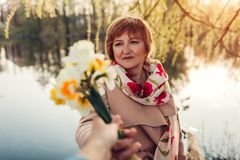 Daughter giving her mother bouquet of flowers. Mother`s day concept stock photography