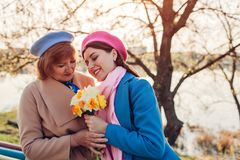 Daughter giving her mother bouquet of flowers. Mother`s day concept stock images