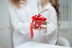 Daughter giving her mother a christmas present stock images