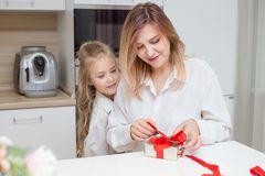 Daughter giving her mother a christmas present stock photo
