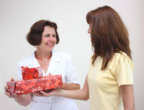 A daughter giving her mother gift. A daughter giving her smiling mother presents isolated on a white background Royalty Free Stock Photography