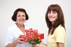 A daughter giving her mother presents. A smiling daughter giving her happy mother presents and flower isolated on a white background Stock Images