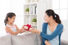 Daughter giving her mother a red ribbon gift box. Mixed race chinese smiling daughter giving her mother a red ribbon gift box want to give mom a surprise at Stock Images
