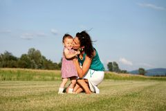 Daughter giving mother flowers. Outdoor shot Stock Images