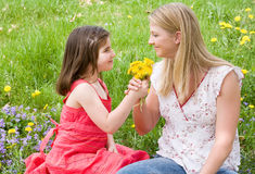 Daughter Giving Mother Flowers. In a Field Stock Photo