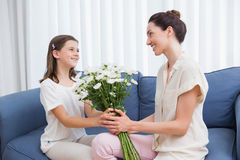 Daughter giving mother white bouquet Royalty Free Stock Image