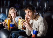 Daughter Giving Shh Expression To Father Using. Annoyed daughter giving shh expression to father using mobilephone in cinema theater Stock Photography