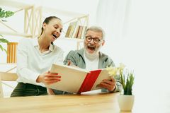 A daughter or granddaughter spends time with the grandfather stock photos
