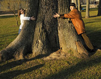 Daughter and granny embrace giant tree Stock Photos