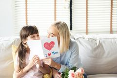 Daughter greeting her Mom with roses and postcard stock photography