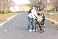 Daughter handing an elderly disabled man groceries Royalty Free Stock Photo