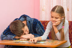 Daughter having fun collecting picture puzzles while dad sleeps next Royalty Free Stock Photo