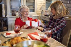 Daughter having gift surprise from senior mother for Christmas stock photo