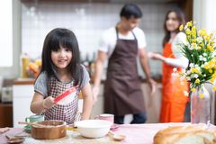 Daughter help parent preparing the bake Family concept. Daughter and parent preparing the bake stock photography